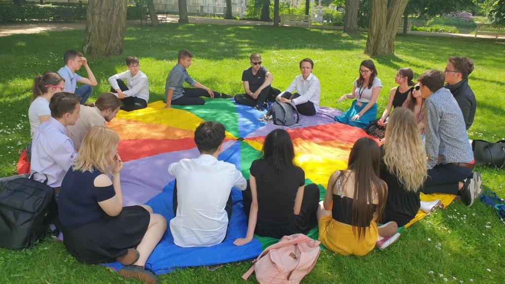 Na zdjęciu uczniowie na kolorowej chuście podczas lekcji muzealnej w Łazienkach Królewskich.