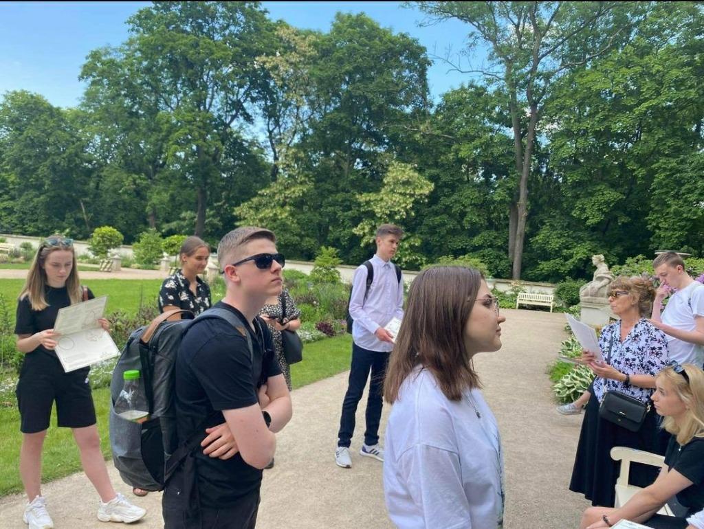 Na zdjęciu uczniowie zasłuchani w opowieści przewodnika podczas lekcji muzealnej w Łazienkach Królewskich.