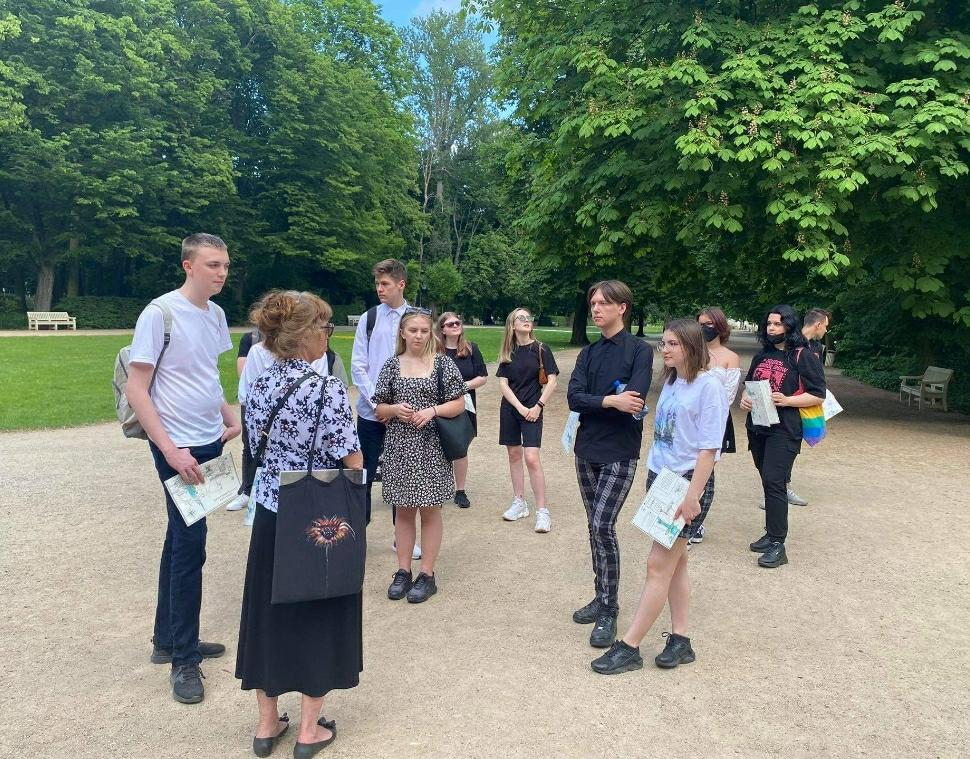 Na zdjęciu uczniowie, zasłuchani w opowieści przewodnika podczas lekcji muzealnej w Łazienkach Królewskich.