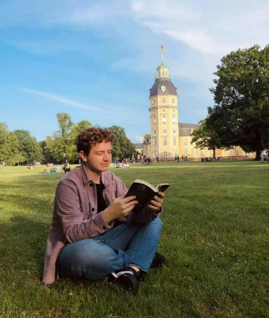 na zdjęciu widać najlepszego czytelnika liceum czytającego książkę w plenerze