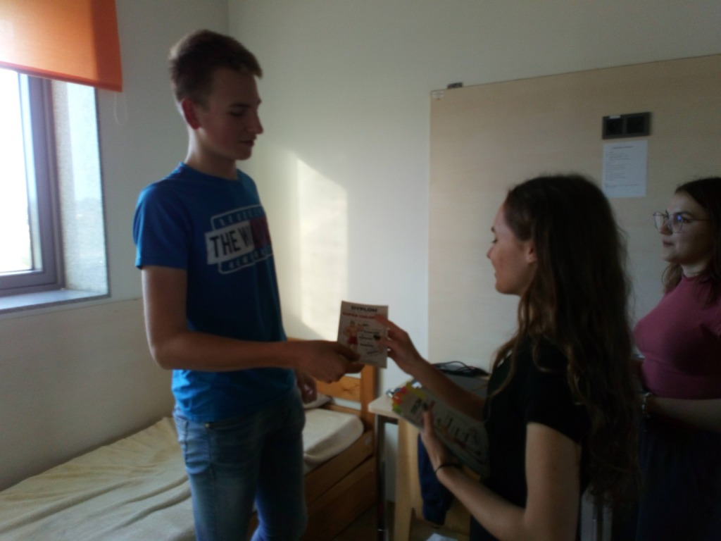Oliwia i Konstancja wręczające koledze  z internatu Dyplom Super Chłopaka z okazji Dnia Chłopaka
